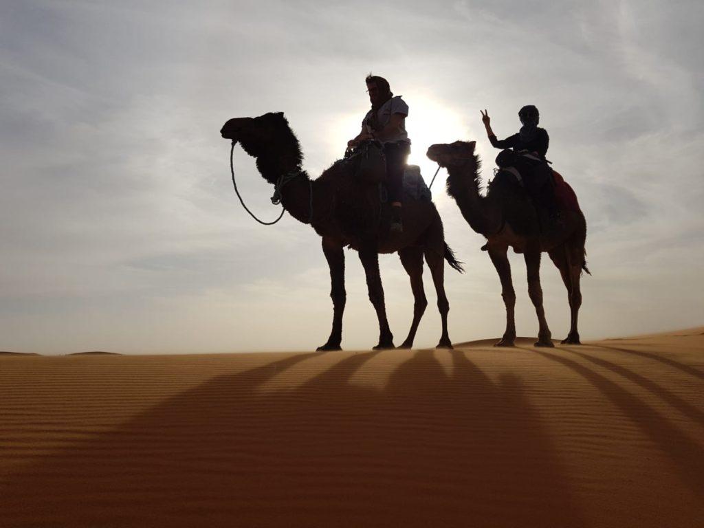 Io e madre a cavallo di due cammelli nel El Chebbi, nel deserto d'oro vicino a Merzouga.