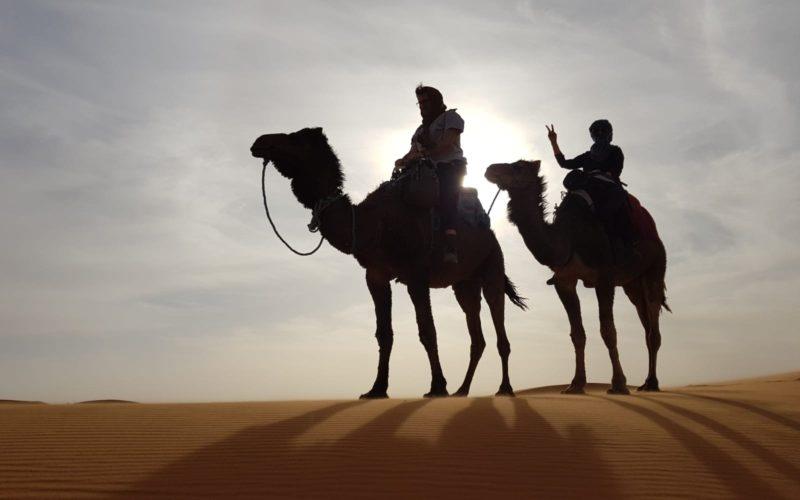 Io e madre a cavallo di due cammelli nel El Chebbi, le sabbie d'oro vicino a Merzouga.