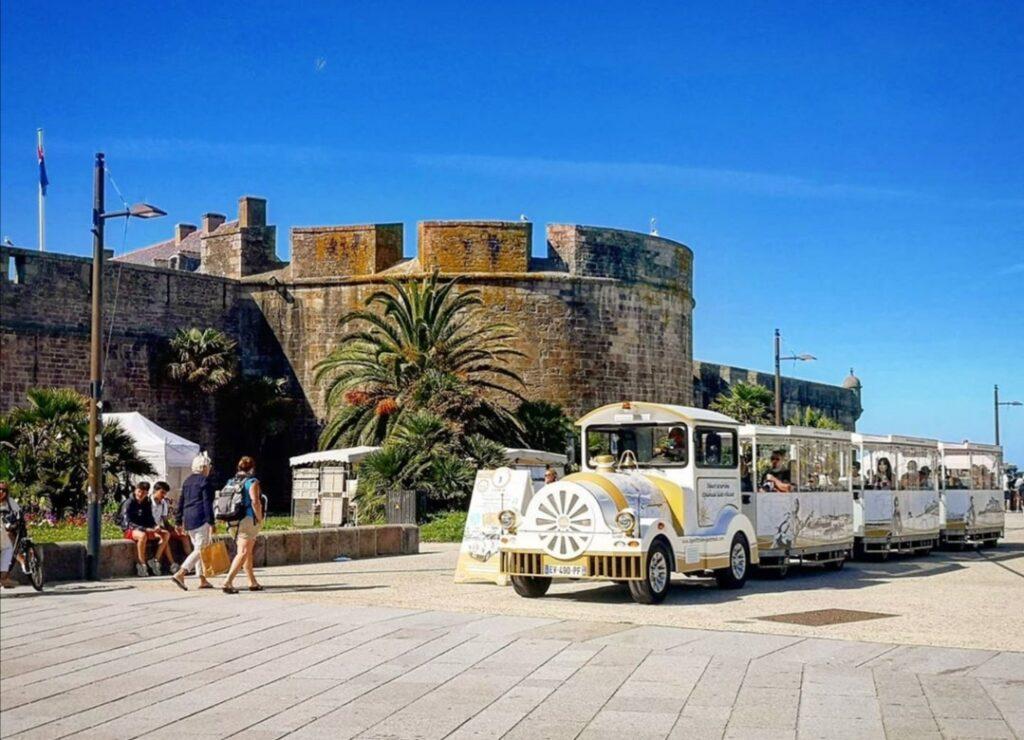 Saint-Malo in Bretagna: il trenino turistico con in sfondo i bastioni del castello della città.